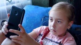 Giochi teenager della ragazza nel telefono mentre sedendosi sul letto video d archivio