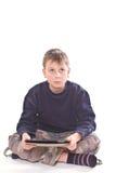 Giochi teenager sul computer della compressa Immagine Stock