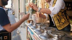 Giochi turchi tradizionali del venditore del gelato con il cliente 4K 10 ottobre 2018 - Istambul, Turchia stock footage