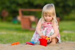 Gioco adorabile del bambino con la pala ed il secchio in sabbia Immagine Stock