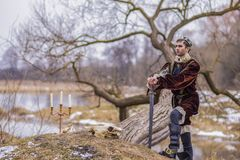 Gioco Art Photography del costume Cavaliere solo In Medieval Outfit che posa nel fondo di Forest Outdoors Against River On fotografie stock libere da diritti