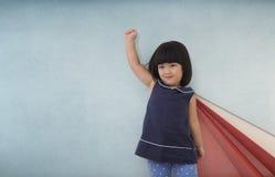 Gioco asiatico della ragazza del bambino del supereroe, bambino con il muro di cemento rosso e blu Immagine Stock