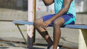 Gioco aspettante sul banco, vita attiva del giocatore di pallacanestro afroamericano muscolare video d archivio