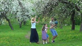Gioco attivo della famiglia con la palla nel giardino di primavera Colpo statico del movimento lento archivi video