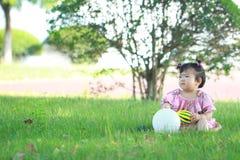 Gioco cinese spensierato della neonata una palla e un pallone sul prato inglese Fotografie Stock