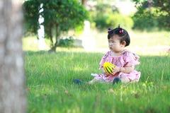Gioco cinese spensierato della neonata una palla sul prato inglese Fotografie Stock