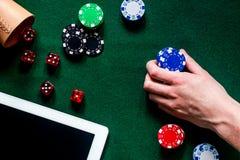 Gioco compulsivo Mano con il chip di mazza e la tastiera vicina dei dadi sul copyspace verde di vista del piano d'appoggio Fotografia Stock