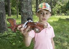 Gioco da bambini con un aereo di legno nella montagna Immagini Stock