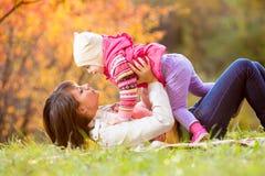 Gioco da bambini della figlia e della donna all'aperto nella caduta Immagine Stock