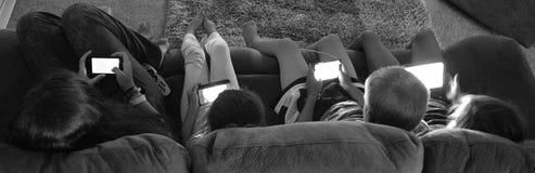 Gioco degli adolescenti sugli apparecchi elettronici Immagine Stock