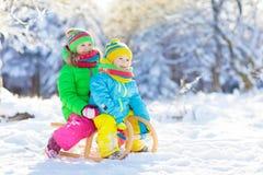 Gioco dei bambini in neve Giro della slitta di inverno per i bambini fotografie stock