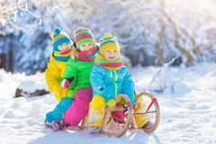 Gioco dei bambini in neve Giro della slitta di inverno per i bambini immagini stock libere da diritti
