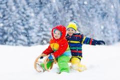 Gioco dei bambini in neve Giro della slitta di inverno per i bambini fotografie stock libere da diritti