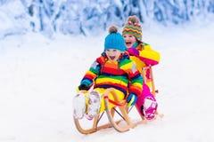 Gioco dei bambini in neve Giro della slitta di inverno per i bambini fotografia stock