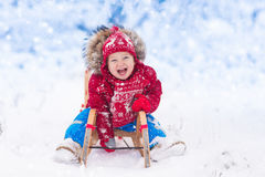 Gioco dei bambini in neve Giro della slitta di inverno per i bambini immagine stock libera da diritti