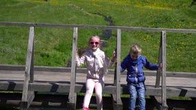 Gioco dei bambini sul ponte sopra la corrente archivi video