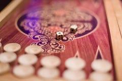 Gioco dei dadi bianchi sul primo piano del bordo di tavola reale con fondo vago Fotografia Stock Libera da Diritti