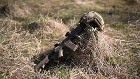 Gioco del airsoft o di guerra l'arma automatica del Sabbia-fucile con un casco del cammuffamento e di mirino si trova sull'erba a stock footage