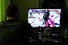 gioco del calcio di sorveglianza dell'uomo sulla TV immagini stock