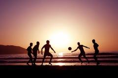 Gioco del calcio di tramonto Immagine Stock