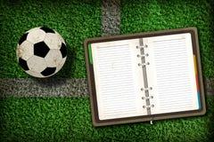 Gioco del calcio e taccuino in bianco Fotografia Stock