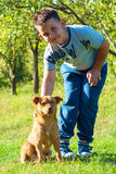 Gioco del cane e del bambino all'aperto all'ambiente di verde del cortile Fotografie Stock