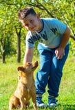 Gioco del cane e del bambino all'aperto all'ambiente di verde del cortile Fotografie Stock Libere da Diritti