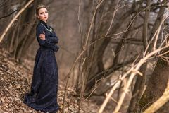 Gioco del costume Giovane femmina castana caucasica in Art Dress con la collana e la corona che posano in Forest Outdoors immagini stock