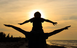 Gioco del figlio e del padre sulla spiaggia di tramonto Immagini Stock Libere da Diritti