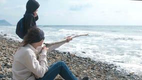 Gioco del figlio e della mamma insieme sulla spiaggia Tiro dai rami come dall'arma stock footage