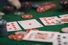 Gioco del poker in mani del ` s degli uomini sulla tavola verde Immagini Stock