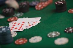 Gioco del poker in mani del ` s degli uomini sulla tavola verde Immagine Stock