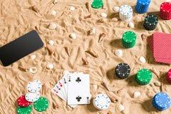 Gioco del poker online sulla spiaggia con astuto digitale e le pile di chip Vista superiore Immagine Stock