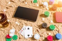 Gioco del poker online sulla spiaggia con la compressa digitale e le pile di chip Vista superiore Immagini Stock