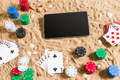 Gioco del poker online sulla spiaggia con la compressa digitale e le pile di chip Vista superiore Fotografia Stock