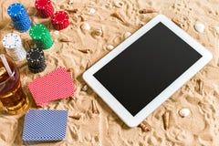 Gioco del poker online sulla spiaggia con la compressa digitale e le pile di chip Vista superiore Fotografie Stock Libere da Diritti