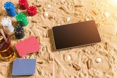 Gioco del poker online sulla spiaggia con la compressa digitale e le pile di chip Vista superiore Immagine Stock