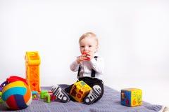 Gioco del ragazzino con i giocattoli sulla coperta sopra bianco Immagini Stock Libere da Diritti