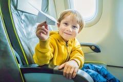 Gioco del ragazzino con l'aereo di carta nell'aeroplano commerciale del jet Fotografia Stock