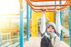 Gioco del ragazzino sul campo da giuoco con il fondo del parco della sfuocatura Fotografia Stock