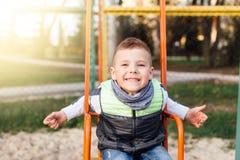 Gioco del ragazzino sul campo da giuoco con il fondo del parco della sfuocatura Immagine Stock Libera da Diritti