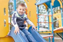 Gioco del ragazzino sul campo da giuoco con il fondo del parco della sfuocatura Fotografie Stock