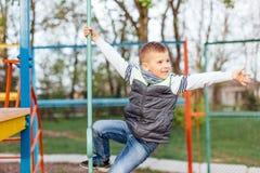 Gioco del ragazzino sul campo da giuoco con il fondo del parco della sfuocatura Immagine Stock