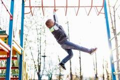 Gioco del ragazzino sul campo da giuoco con il fondo del parco della sfuocatura Fotografia Stock Libera da Diritti