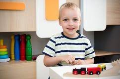 Gioco del ragazzo del bambino con il treno di legno nell'asilo Fotografia Stock Libera da Diritti