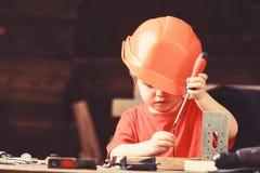 Gioco del ragazzo come il costruttore o riparatore, lavoro con gli strumenti Bambino che sogna della carriera futura nell'archite immagini stock