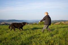 Gioco del ragazzo con il cane Fotografie Stock Libere da Diritti