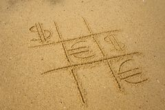 gioco del Tic-TAC-dito del piede con il gioco dei simboli del dollaro e dell'euro sulla sabbia Fotografia Stock