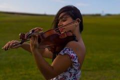 Gioco del violino nel parco Immagini Stock