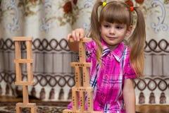 Gioco della bambina con i blocchi di legno Immagine Stock